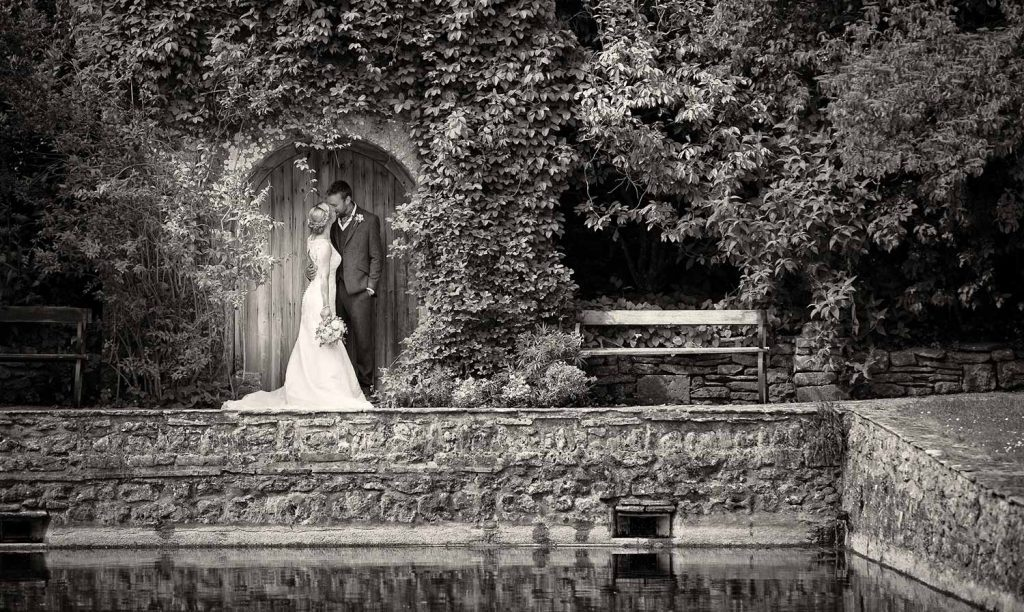 First kiss at the reflecting pool at Mapperton, a Dorset Wedding Venue