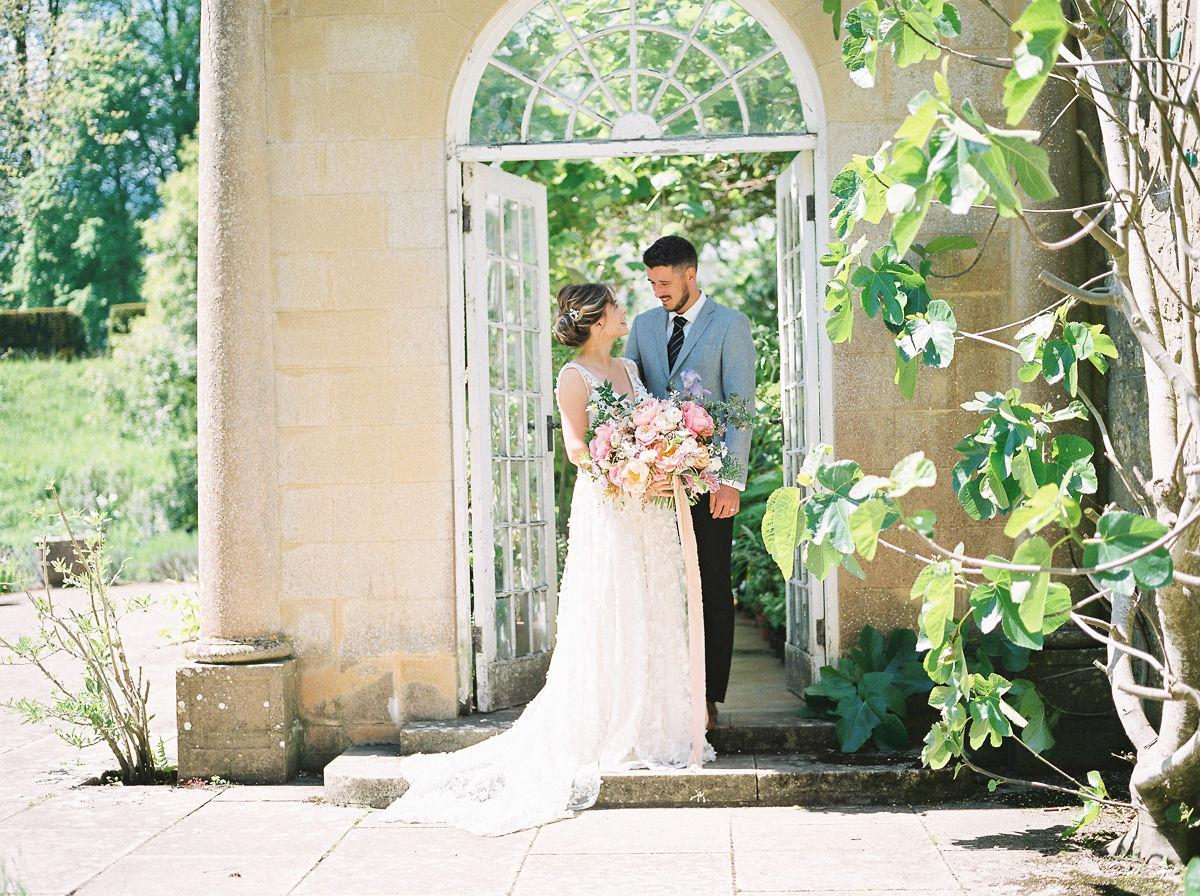 Wedding couple at doors of Orangery in the gardens